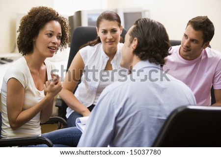 Man giving lecture to three people in computer room - stock photo