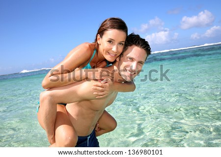 Man giving piggyback ride to girlfreind in Caribbean sea