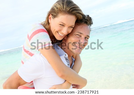 Man giving piggyback ride to girlfriend at the beach - stock photo