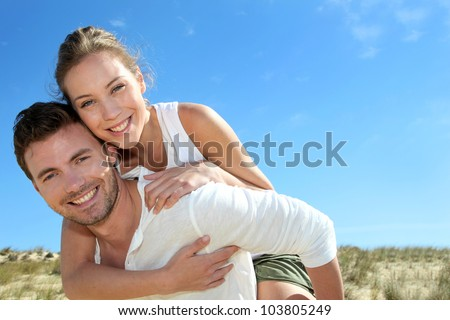 Man giving piggyback ride to girlfriend on a sand dune - stock photo