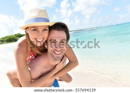 Man giving piggyback ride to girlfriend on Caribbean beach - stock photo