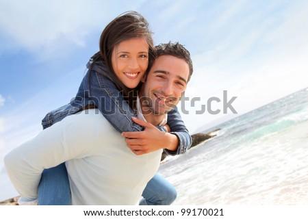 Man giving piggyback ride to girlfriend on the beach - stock photo