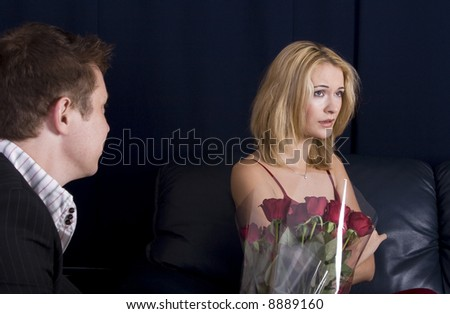 Man giving roses as gift to an upset blond girl who is ignoring him - stock photo