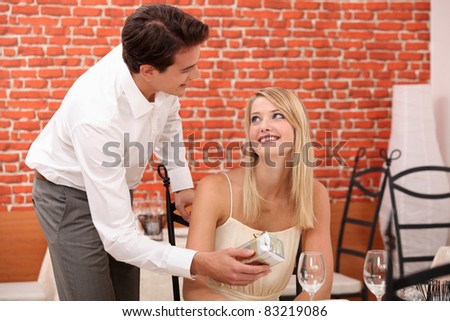 Man giving surprise gift to woman in restaurant - stock photo
