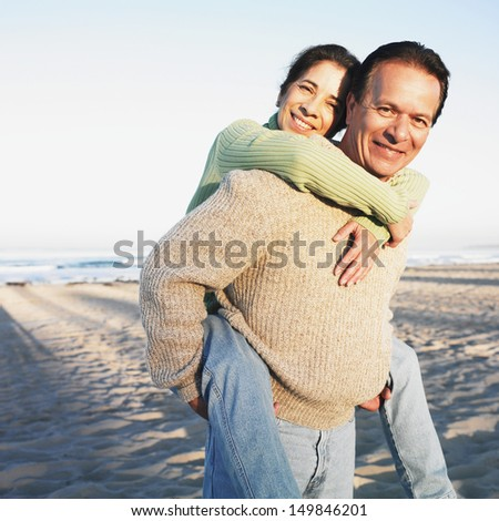 Man giving wife piggyback ride at beach