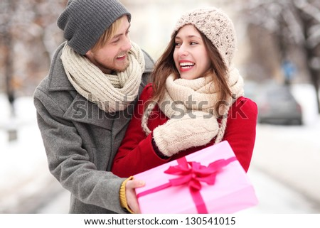 Man giving woman a surprise gift - stock photo
