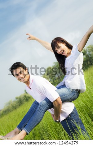 Man giving woman piggyback in meadow, laughing. Narrow focus on his eye. - stock photo