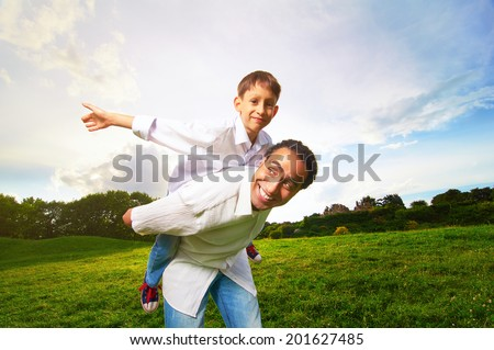 Man giving young boy piggyback ride outdoors smiling. - stock photo