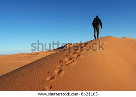 Man go up in sand desert - stock photo