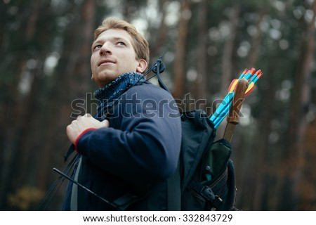 Man go with hunter bow in forest looking around