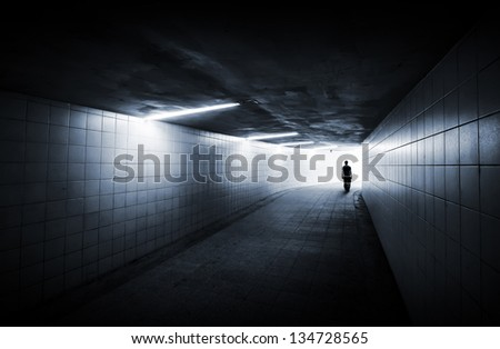 Man goes on underground passage with neon lights and glowing end - stock photo