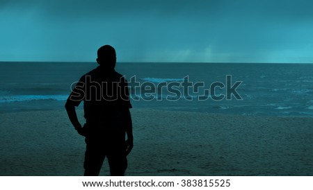 Man goes to the sea on dark sand beach under beautiful colorful cloudy sky - stock photo