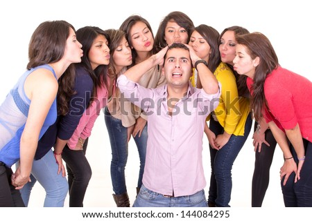 Man going nuts with eight women kissing him - stock photo