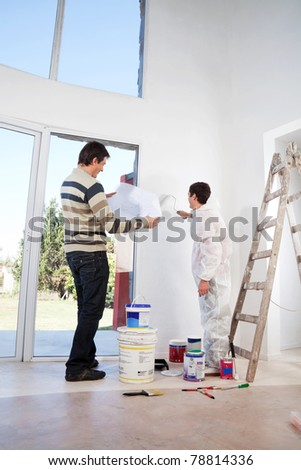 Man going through house plan while painter painting the wall - stock photo