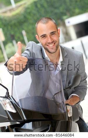 Man going to work on motorcycle - stock photo