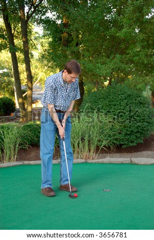 Man golfing at a miniature golf place in summertime. - stock photo
