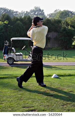 Man golfing - driving ball  from the tee with a seven iron. - stock photo