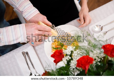 Man grating cheese over pasta, domestic setting (selective focus on the cheese grater) - stock photo