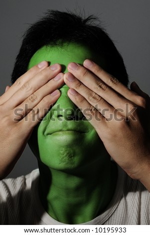 Man green with envy hiding his emotions - stock photo