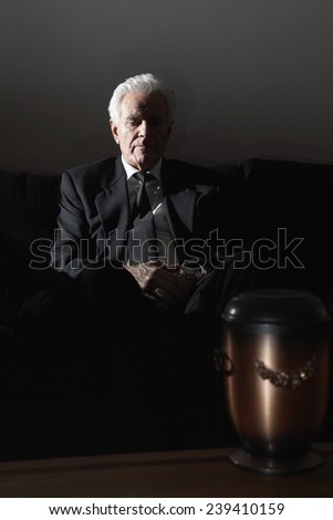 Man Grieving near Funeral Urn - stock photo