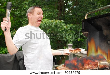 Man grilling on barbeque when flames get out of control - stock photo