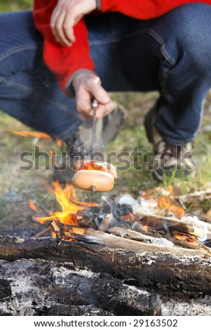 Man grilling sausage on bonfire