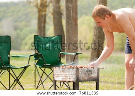 Man grilling shish kebab outdoor in park - stock photo