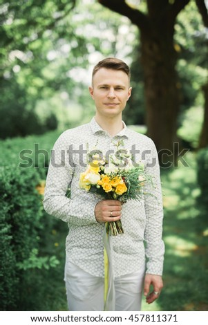 Man, groom posing with perfect wedding bouquet - stock photo