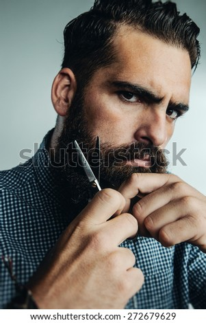Man grooming his beard with scissors