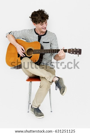 Man guitarist player sitting and playing guitar