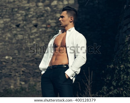 Man half face bare-chested young handsome sensual model in white shirt gaped open poses with hands in black trouser pockets outside on masonry background  - stock photo