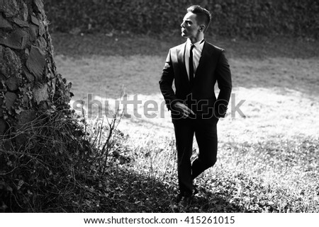 Man half face young handsome elegant model in suit with skinny necktie poses with hand in trouser pocket one leg backward black and white on landscape on grey background - stock photo