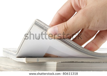 man hand browsing through stack of magazines - stock photo