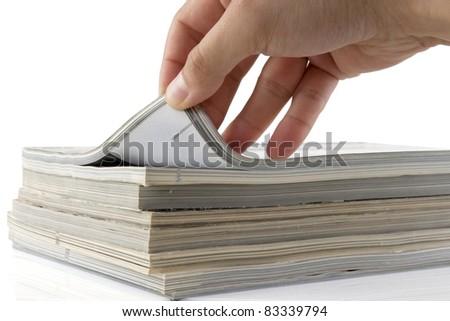 man hand browsing through stack of magazines - stock photo