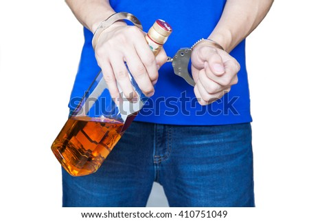 Man hand carrying alcohol drink with handcuffs - Drunk driving, alcohol addiction effect concept (Focus on Handcuffs) - stock photo