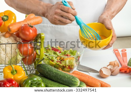 man hand cook make omelette, beating whisk eggs, on kitchen, closeup photo - stock photo