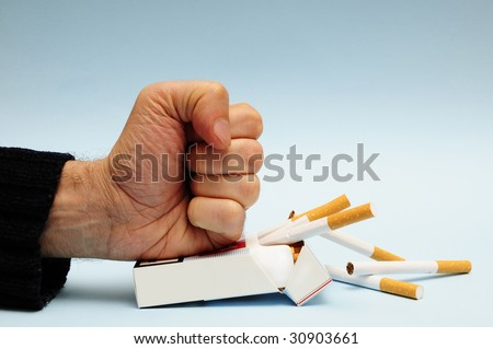 man hand crushing a packet of cigarettes, stop smoking concept - stock photo