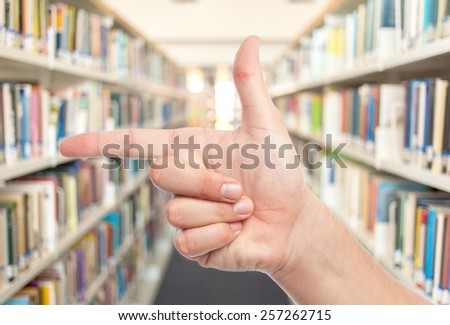 Man hand doing a gun gesture. Over library background - stock photo