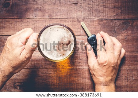 Man hand drinking beer and holding car keys - stock photo