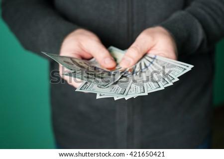 man hand giving 100 dollar bills in studio - stock photo