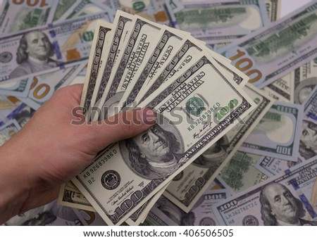 man hand giving 100 dollar bills on a background of 100 dollar bills - stock photo