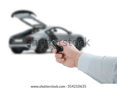 Man hand holding a black remote control key near a new car with an open hood on a white background
