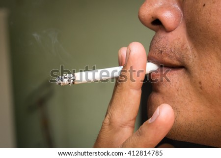 man hand holding a cigarette with smoke  Selective focus. - stock photo