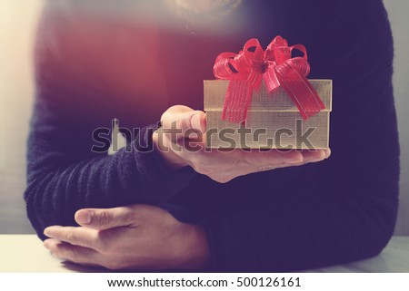 man hand holding a gift box in a gesture of giving.blurred background,vintage effect