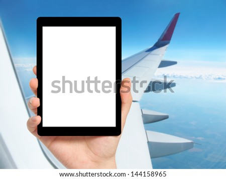 man hand holding a tablet computer with isolated screen against the background of the window with blue sky and airplane wing - stock photo