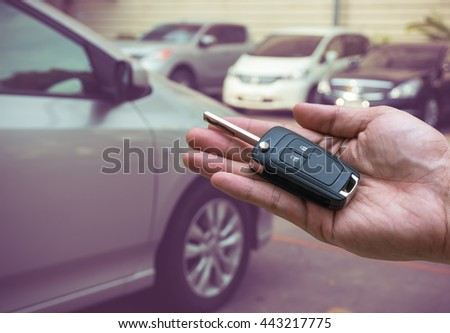 Man hand holding and giving a car key remote on photo blurred of car, transportation and ownership concept - stock photo