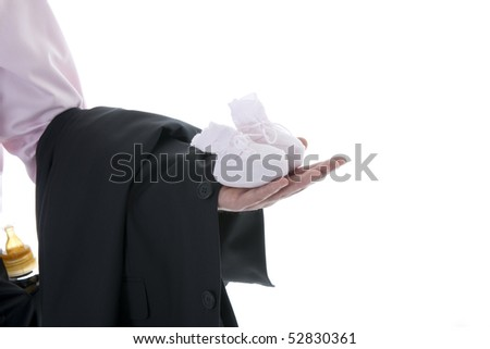 Man hand holding baby shoe and business jacket, milk bottle on his trousers pocket. Concept: modern man, multi-tasking - stock photo