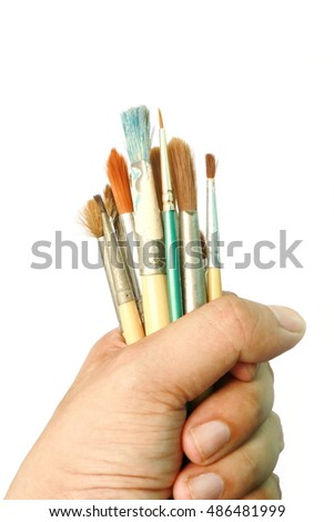 man hand holding brush isolated on white background, Hand hold many brush for oil color paint. Artist tool and equipment.