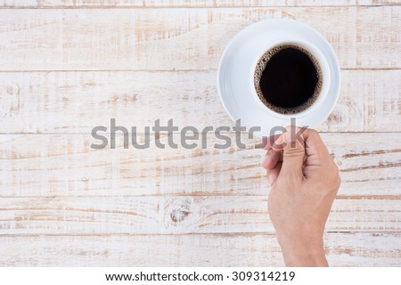 Man Hand holding Cup of coffee on white  wooden table background.copy space - stock photo