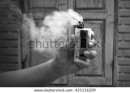 Man hand holding electric cigarette bottle in front of vintage wood windows and old brick wall, electric cigarette is a part of quit smoking program for cigarette smoker, black and white version. - stock photo